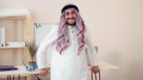 Un especialista árabe mira la cámara en la oficina el hombre de negocios de Oriente Medio trabaja de la oficina Sirva la sonrisa metrajes