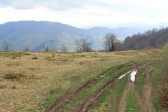 Un espejo-charco en un camino en una colina cárpata foto de archivo