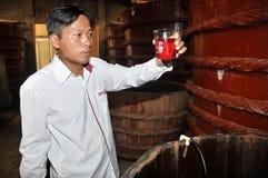 Un esperto sta controllando la qualità del campione della salsa di pesce che è una salsa tradizionale nel Vietnam, da un carro ar Immagini Stock Libere da Diritti