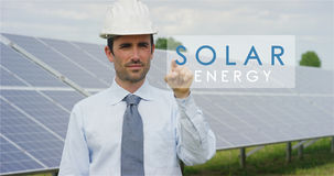 Un esperto tecnico futuristico in pannelli fotovoltaici solari, seleziona la funzione a energia solare del ` del ` facendo uso di Immagini Stock Libere da Diritti