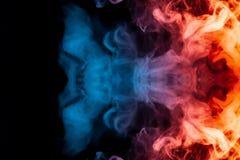 Un'esplosione dinamica dei soffi di fumo dell'arancia e della r blu-chiaro fotografia stock