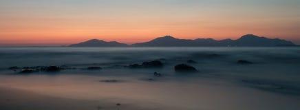 Un'esposizione lunga del mare all'ora dorata, come il sole mette dietro una montagna fotografie stock
