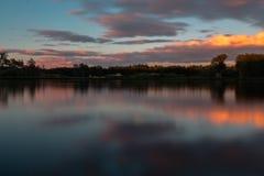 Un'esposizione lunga di un tramonto variopinto con le riflessioni e un cielo drammatico immagine stock libera da diritti