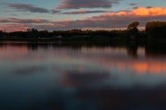Un'esposizione lunga di un tramonto variopinto con le riflessioni e un cielo drammatico immagine stock