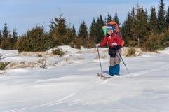 Un esquí del campo a través de la mujer en la montaña Foto de archivo