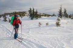 Un esquí del campo a través de la mujer en la montaña Fotografía de archivo