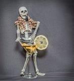 Un esqueleto detrás del vidrio con el alcohol flúido y que lleva a cabo llaves del coche en su mandíbula Foto de archivo libre de regalías