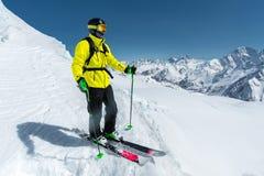 Un esquiador parasitario en equipo completo se coloca en un glaciar en el Cáucaso del norte contra la perspectiva del caucásico Imagenes de archivo