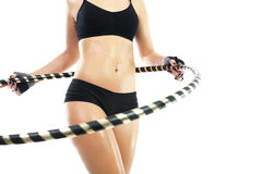 Un estómago plano y las nalgas firmes, la mujer entrena con el salto de Hula de la rueda Fotografía de archivo