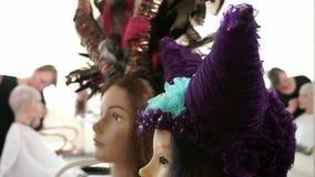 Un estante con las cabezas del maniquí en las pelucas coloridas almacen de video