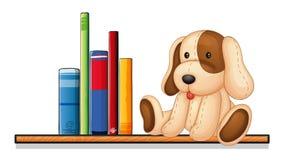 Un estante con libros y un juguete Imagenes de archivo