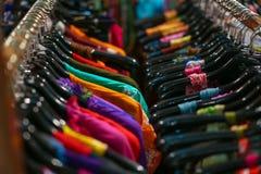 Un estante de camisas coloridas colgó para la venta Imágenes de archivo libres de regalías