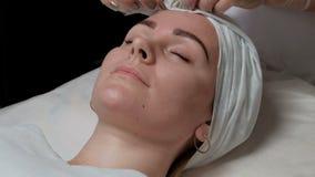 Un estetista con una fasciatura bianca copre i capelli sulla testa del ` s del cliente Il fronte di bella ragazza europea in un s stock footage
