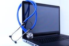 Un estetoscopio médico cerca de un ordenador portátil en una tabla de madera, en blanco Foto de archivo