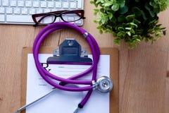 Un estetoscopio médico cerca de un ordenador portátil en un de madera Foto de archivo