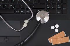 Un estetoscopio, píldoras y yeso en un ordenador portátil Imagen de archivo