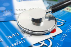 Un estetoscopio por las tarjetas de un crédito Fotografía de archivo libre de regalías