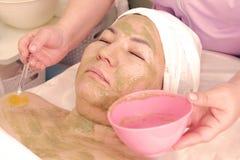 Un esthéticien applique un masque d'algues vertes à un visage de la femme s La femme asiatique prend des traitements de station t photo stock