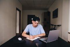 Un estudiante adolescente escribe una tarea en un cuaderno que se sienta en una tabla cerca del ordenador El estudiante estudia e Imágenes de archivo libres de regalías