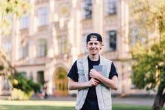 Un estudiante adolescente sonriente con una libreta que se coloca en un campus cerca de su universidad En el fondo del caspouse Imágenes de archivo libres de regalías
