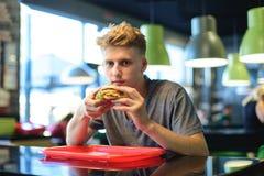 Un estudiante come los alimentos de preparación rápida en un bistro Una hamburguesa apetitosa en las manos de un hombre joven Una Fotografía de archivo