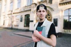 Un estudiante concentrado con un cuaderno en sus manos se coloca en la entrada a su universidad Foto de archivo libre de regalías