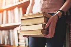 Un estudiante de la chica joven que busca la literatura cerca de los estantes en la biblioteca vieja fotografía de archivo