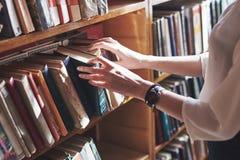 Un estudiante de la chica joven que busca la literatura cerca de los estantes en la biblioteca vieja imagenes de archivo