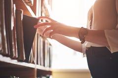 Un estudiante de la chica joven que busca la literatura cerca de los estantes en la biblioteca vieja imágenes de archivo libres de regalías