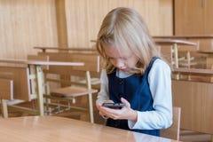 Un estudiante de primera clase en la escuela juega al juego en el teléfono emociones de alumnos Fotografía de archivo
