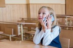 Un estudiante del primer grado en la escuela habla por el teléfono emociones de colegialas Fotos de archivo