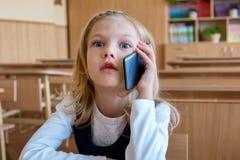 Un estudiante del primer grado en la escuela habla por el teléfono emociones de colegialas Fotografía de archivo