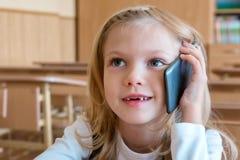 Un estudiante del primer grado en la escuela habla por el teléfono emociones de colegialas Imagen de archivo libre de regalías