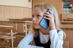 Un estudiante del primer grado en la escuela habla por el teléfono emociones de colegialas Imágenes de archivo libres de regalías