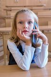 Un estudiante del primer grado en la escuela habla por el teléfono emociones de colegialas Fotografía de archivo libre de regalías