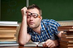 Un estudiante desaliñado cansado y torturado en vidrios está durmiendo en una tabla con las pilas de libros imagen de archivo