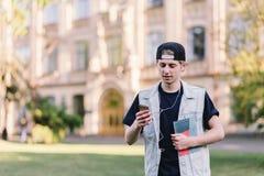 Un estudiante elegante, interesado en un casquillo lleva un teléfono móvil y escucha la música en el fondo de la universidad Foto de archivo
