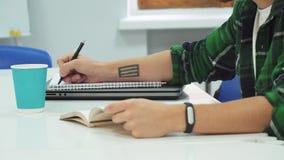 Un estudiante elegante lee un libro y escribe la información importante fuera de ella almacen de video