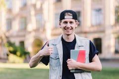 Un estudiante elegante sonriente muestra los pulgares para arriba en el fondo de un campus de la universidad Foto de archivo