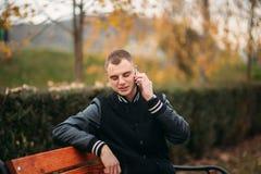 Un estudiante en una chaqueta negra se sienta en un parque en un banco y utiliza el teléfono Muchacho hermoso Foto de archivo libre de regalías