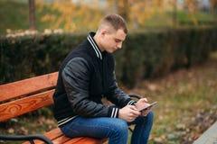 Un estudiante en una chaqueta negra se sienta en un parque en el banco y la tableta del uso Muchacho hermoso Foto de archivo