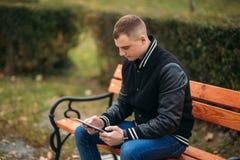 Un estudiante en una chaqueta negra se sienta en un parque en el banco y la tableta del uso Muchacho hermoso Imagenes de archivo
