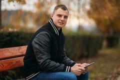Un estudiante en una chaqueta negra se sienta en un parque en el banco y la tableta del uso Muchacho hermoso Fotografía de archivo libre de regalías