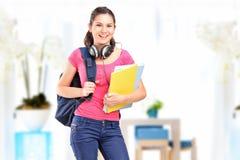 Un estudiante femenino sonriente con los auriculares Fotografía de archivo libre de regalías