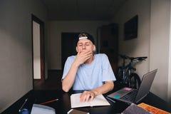 Un estudiante joven bosteza mientras que lee un libro El estudiante quiere dormir Preparación Enseñanza en casa Fotografía de archivo
