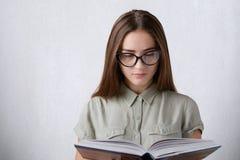 Un estudiante joven con la camisa que lleva larga y las lentes del pelo recto que llevan a cabo una lectura del libro algo Una le Imagenes de archivo