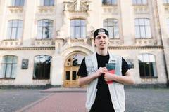 Un estudiante joven confiado con un cuaderno en sus manos se coloca contra la perspectiva de la entrada de la universidad Fotos de archivo