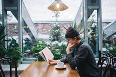 Un estudiante joven en casquillo y camisa que lee un libro y que bebe el café en un café hermoso con el invernadero Fotos de archivo