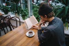 Un estudiante joven en un casquillo enseña al tema de un libro con una taza de té Fotografía de archivo