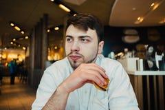 Un estudiante joven en un restaurante acogedor que come la hamburguesa de los alimentos de preparación rápida Fotografía de archivo libre de regalías